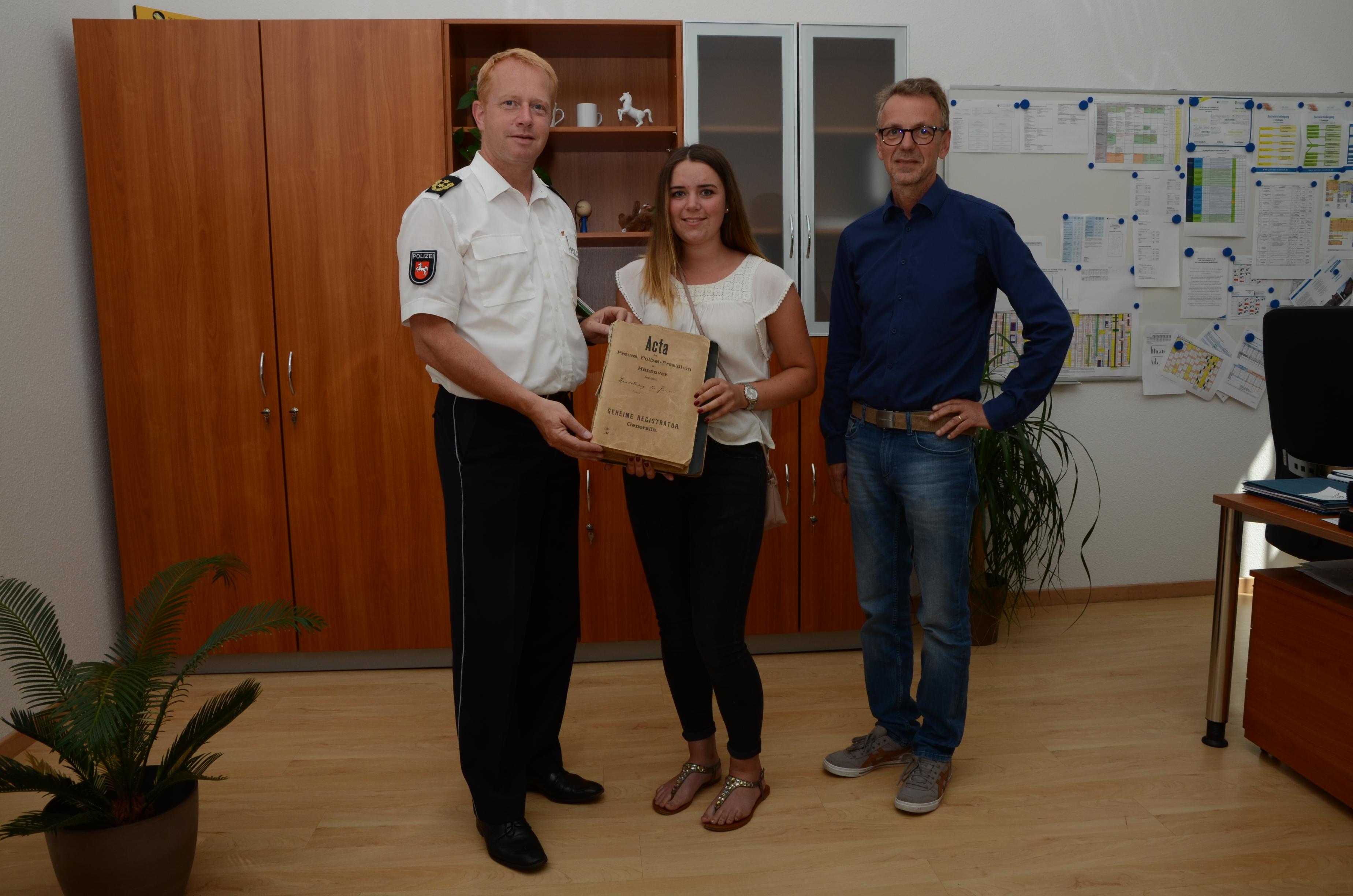 Direktor Carsten Rose nimmt im Beisein von Dr. Götting die historische Akte von der zukünftigen Polizeistudentin Maurien Lupke entgegen.